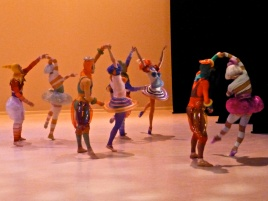 Rainbow colored figures dance