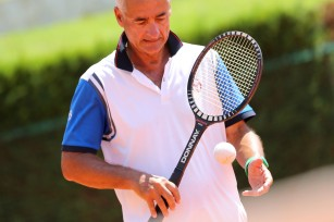 MCCC tennis pro Jacques Vincileoni with a vintage wooden racket and white tennis ball @Erika Tanaka