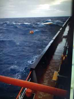 Omar Samra and Omar Nour are seen floating in their life raft with their capsized rowing boat behind them. Taken from the deck of the 'Kefalonia_ during the 4 hour rescue