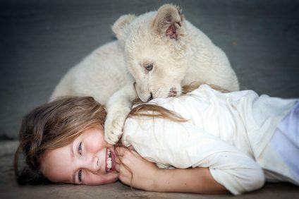 Daniah De Villiers (Mia) with lion cub Charlie during the filming @copyright Coert WiechersGalatÇe Films-Outside Films